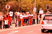 People in red. Protestors line the streets outside the Japanese Embassy in Cape Town. Photo: Spike